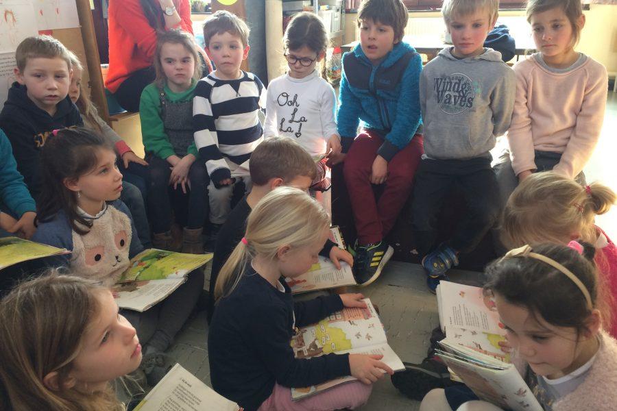 De kinderen van het eerste leerjaar a lezen sprookjes voor in de derde kleuterklas.