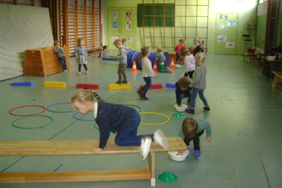 De kleuters van de Bijtjesklas spelen met kastanjes in de turnzaal bij juf Els.