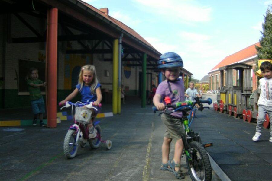 Fietsen met een meegebrachte (loop)fiets, step of met een fietsje van de school.