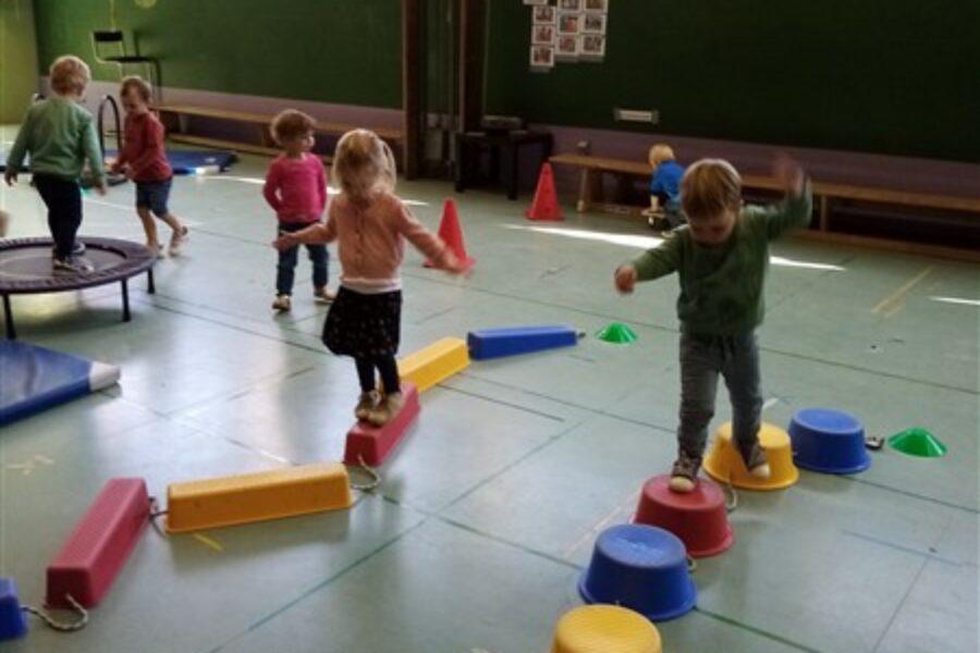 De kinderen van de Bijtjesklas oefenen hun evenwicht in de turnzaal bij juf Els
